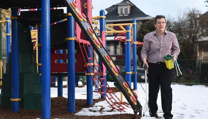 Veronica Light carries a sharps box as she checks a playground outside the Strathcona Community Centre for trash, such as used needles, that could pose a hazard to children. Photo Dan Toulgoet